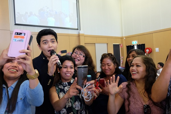 AU-Wagga Wagga-Daryl Ong taking a selfie photo with the audience while performingMR